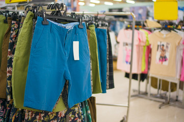 Shorts of different colors on hangers in store