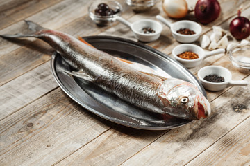 Fish and spices on wooden background