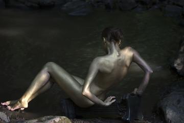 Gold woman near water