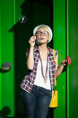 cheerful hipster girl blowing soap bubbles on street