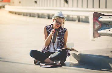 stylish hipster girl sitting on street and reading book
