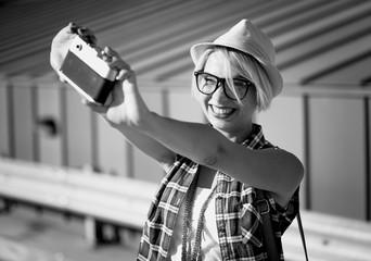 smiling hipster girl making selfie on vintage film camera