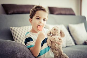 Retrato de niño mirando a cámara, 3 años, sentado en el salón comiendo una piruleta con su perrito de peluche