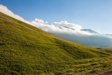 Pendio di montagna, nella luce del tramonto. Cielo blu con nuvole sullo sfondo