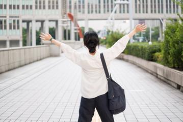 都会の歩道で両手を挙げる女性
