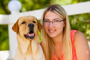 portrait of Beautiful young girl with her dog labrador retriever outdoor in summer beautiful park