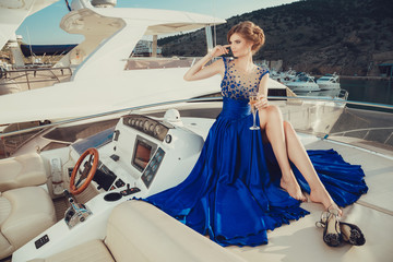 Beautiful young sexy girl in a dress and makeup, summer trip on a yacht with white sails on the sea or ocean