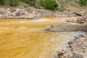Orange hued river water due to an accidental spill of toxic mine waste by the EPA