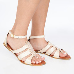 beige leather sandals with gold applied on feet the mujere on white background
