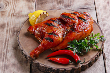 Grilled  half chicken barbecue on a wooden surface