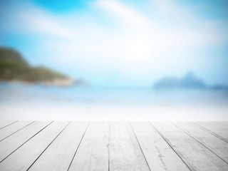 White wood floor with blurred sea background.