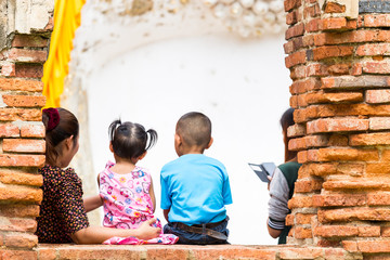 Cute family sit on the wall of old buddha statue at Wat Yai Chaimongkol in Ayuthaya Thailand,This picture was shoot in 1/8/2015