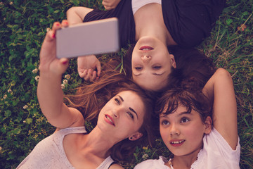 Group of two young woman and child lying on the grass and taking selfie