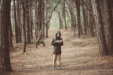 Hiker woman with tablet walking outdoor