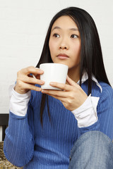 A woman holding a coffee or tea cup.