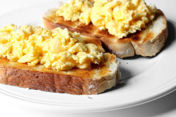 Scrambled egg on toast. Scrambled egg on toast on a plate.