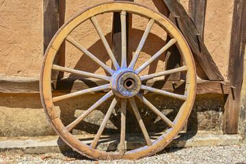 roue en bois contre mur habitation