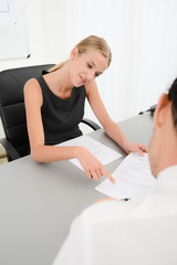 attractive young business woman with customer in office signing an agreement sales contract