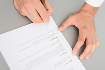 close-up shot of hands signing a contract on desk in office