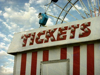 aged and worn vintage photo of carnival ride and ticket booth