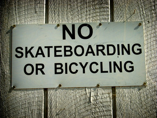 aged and worn vintage photo of no skateboarding sign