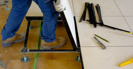 worker carries a floating floor on steel feet, resting on the structure of a slab of porcelain tile.