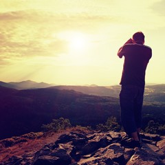 Professional photographer in jeans and shirt  takes photos with mirror camera on peak of rock. Dreamy landscape, orange  Sun at horizon