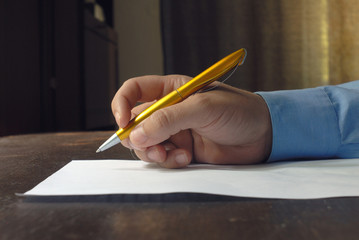 Human males hand holding pen near sheet of paper