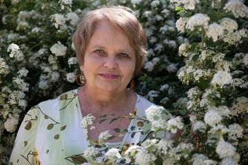 Senior woman under white flower of Spiraea shrub in a garden