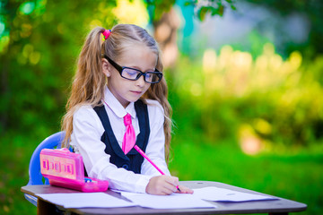 Adorable little school girl at desk with notes and pencils