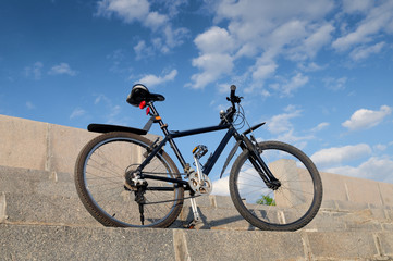 Bike stands on the stone steps on the background of blue sky
