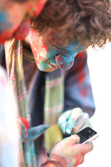 Closeup of colorfully painted clowns reading messanges on mobile phone