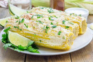 Mexican corn with butter, mayonnaise, parmesan, chili, cilantro, and lime