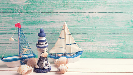 Decorative lighthouse,  sailing boats and marine items on wooden