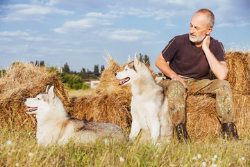 Farmer after a hard day's work. Old man with a beard sitting on a haystack with their dogs, enjoying summer sunset. Siberian Husky in the countryside. Harmony between man and nature.