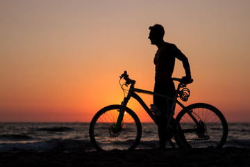 at sunset silhouette of a sportsman on a bike