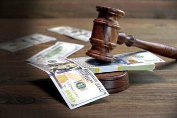 Bundle Of Money, Judges Gavel And Soundboard On Wooden Table