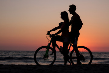 silhouette of couple bike at sunset