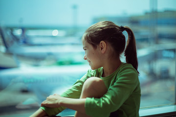 Child at the airport near the window looking at airplanes and waiting for time of flight.