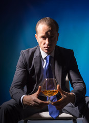 A man in a suit with a glass of spirits