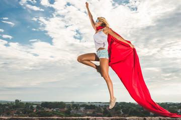 Young woman posing as superhero or wonderwoman