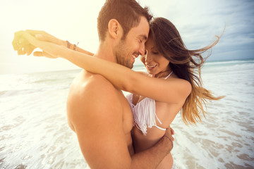 young happy couple with draw heart on tropical beach