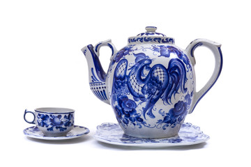 Porcelain teapot, cup and saucer in folk style painted blue on white background