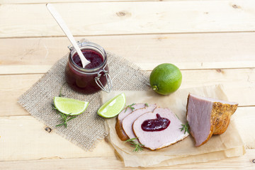 Home made organic cherry jam confiture, smoked meat, rosemary and lime on a wooden table