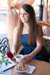 Beautiful young woman with cup of at a cafe