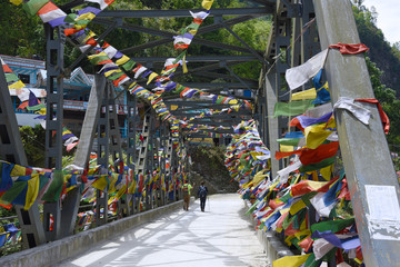 the travelers are walking through bridge to Poon Hill , Nepal