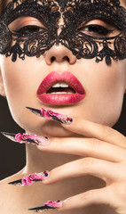 Beautiful girl in mask with long nails and sensual lips. Beauty