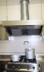 fume Extractor hood in the industrial kitchen with pots on the s