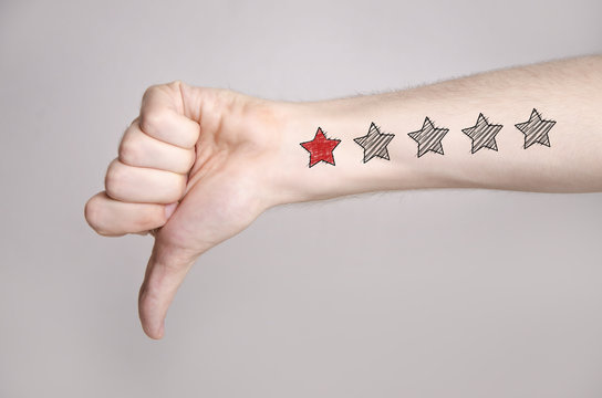 Man hand showing thumbs down and one star rating on the arm skin