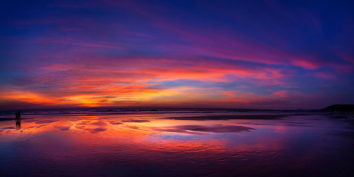 Sunset on fire. Really bright and colorful sunset at the sea with reflection of the skies in the water.